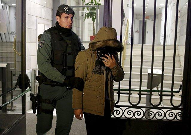 一名女嫌疑人和一名西班牙警官正走出中国工商银行马德里分行
