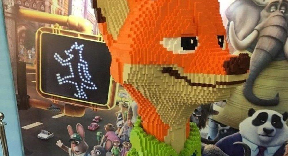 """在中國寧波舉辦的樂高博覽會(Lego Expo)開幕一小時後,一名小遊客就打碎了一個展品——動畫片《瘋狂動物城》中的角色——狐狸尼科的大型塑像。 這個雕塑作品的作者花了三天時間才做出這個所有動畫片支持者熟知的人物形象。他在自己的微博中承認,塑像""""被打碎了"""",他當時看到,自己用大量磚塊製成的作品""""散落""""在展位四周。 與此同時,這名作者拒絕了認為是自己孩子因笨拙而造成過失的孩子的父母的道歉賠償。 這座狐狸雕塑的價值"""