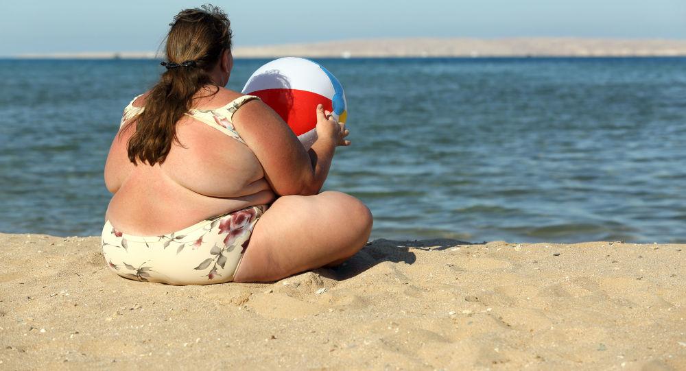 一个在沙滩上的孤独肥胖女子