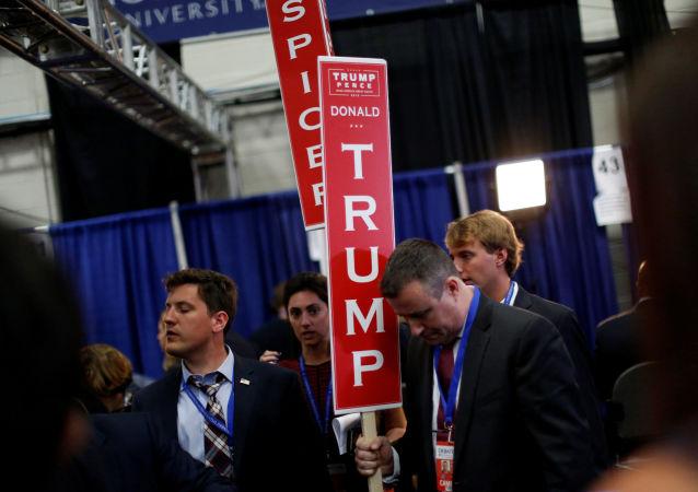 Сотрудники с плакатами после первых дебатов кандидатов в президенты США Дональда Трампа и Хиллари Клинтон