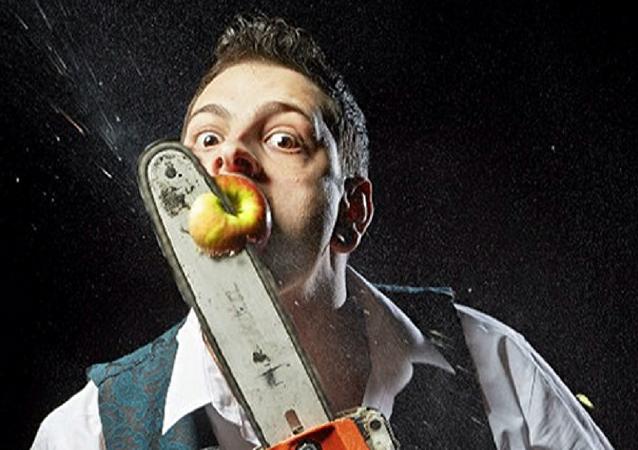 英国人约翰尼•斯特兰奇成为一分钟内用电锯割掉嘴里苹果最多的人