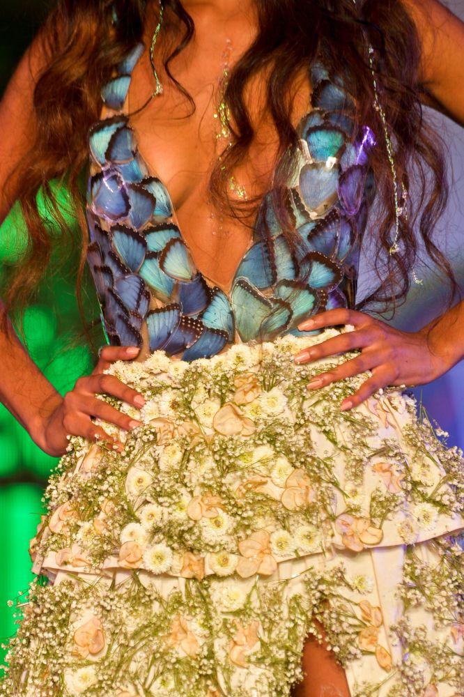 模特身穿由花、果实、叶子和回收品制成的服饰走上T台。