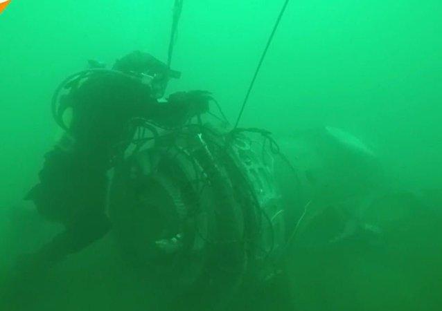 紧急情况部潜水员正在水底搜寻和打捞图–154飞机的残骸。