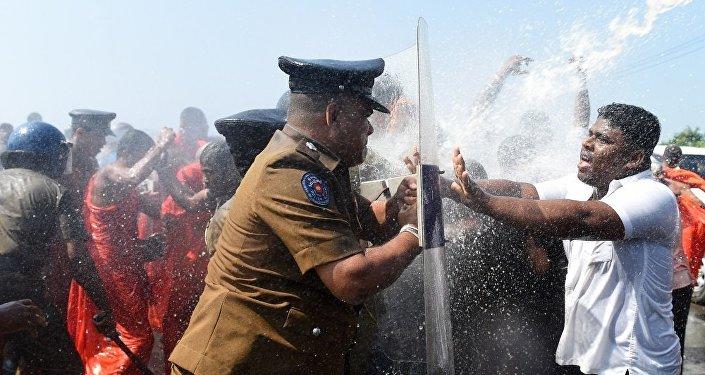 警方使用了高压水炮,试图驱散农民和佛教僧侣以及支持政府在港口附近建设工业园的人。