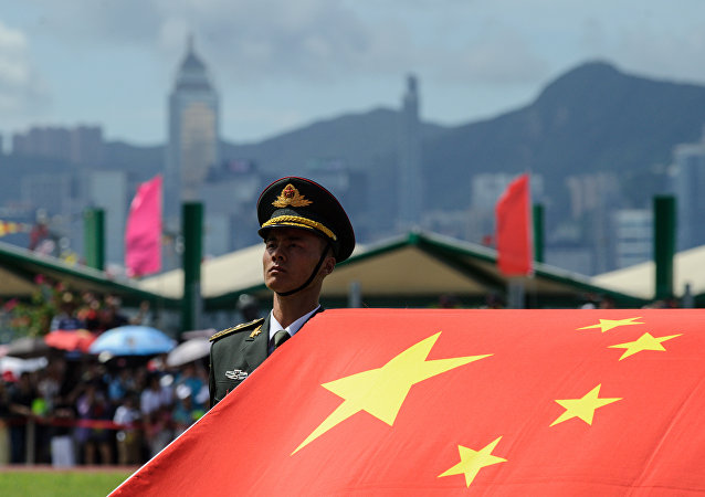 A PLA soldier stands to attention with the Chinese flag