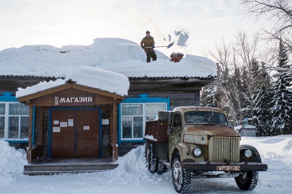 一名男子在清扫博布罗夫卡村商店房顶上的积雪