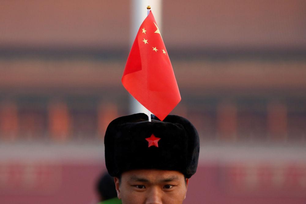 一名男子在天安门广场上手持国旗