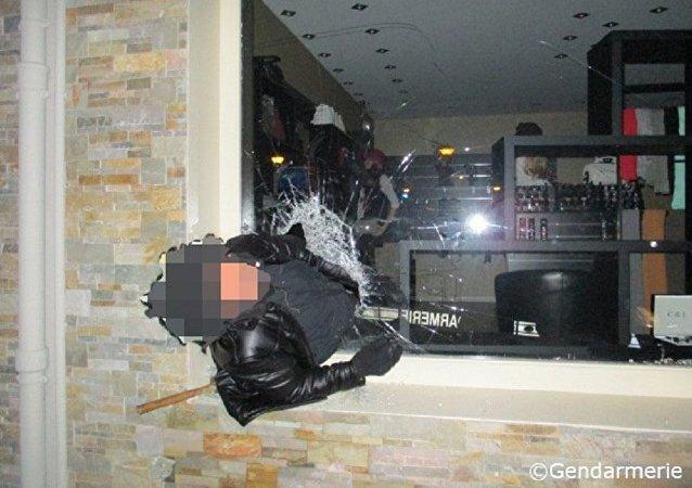 笨小偷进商店抢劫被卡在橱窗上