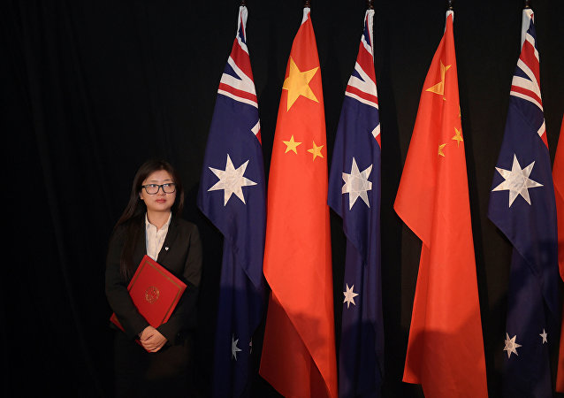 A woman holding a copy of the free trade agreement (FTA) stands next to national flags of China and Australia
