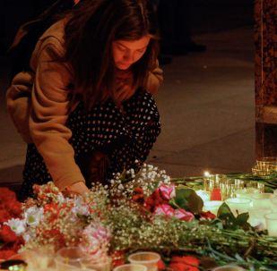 """一名女子在地铁""""救世主站""""的前厅入口处点燃蜡烛,悼念圣彼得堡地铁爆炸案的遇难者"""