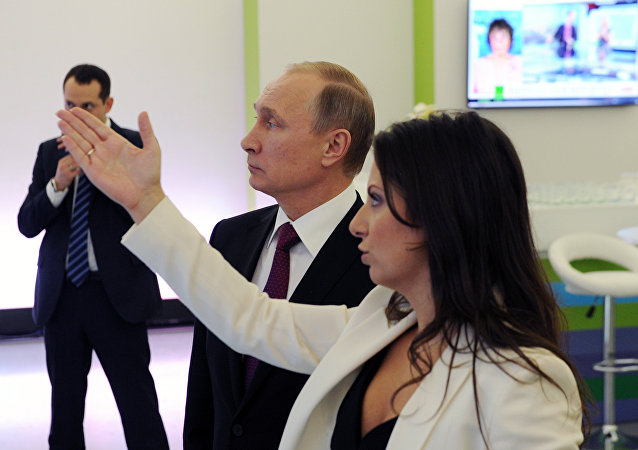 Russian President Vladimir Putin and Editor-in-Chief of the RT (Russia Today) television channel Margarita Simonyan at the exhibition to mark the channel's 10th anniversary