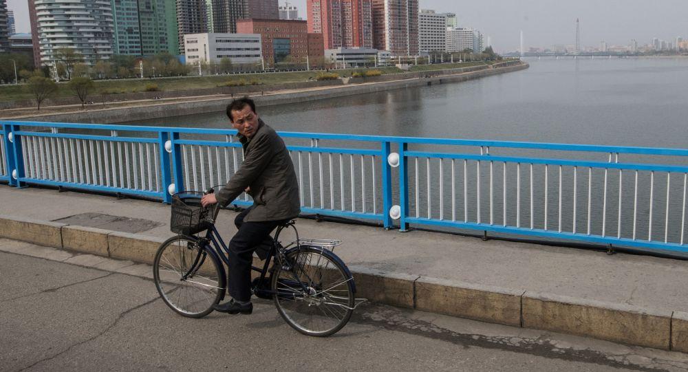 Мужчина едет на велосипеде по одному из мостов в Пхеньяне