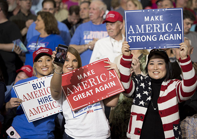Supporters take selfies and hold placards as US President Donald Trump arrives to address a 'Make America Great Again' rally