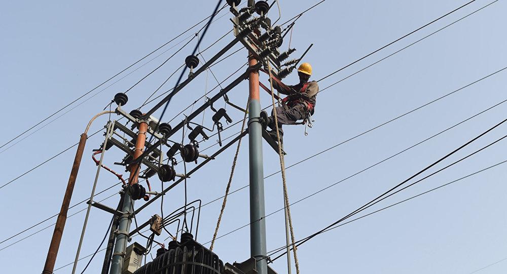 Pakistani technicians of the Karachi Electric Corporation work on a high voltage line in Karachi