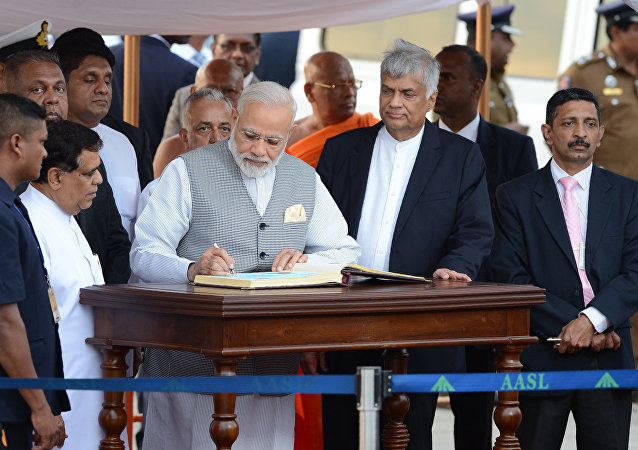India's Prime Minister Narendra Modi (C) is watched by Sri Lankan Prime Minister Ranil Wickremesinghe (3R)