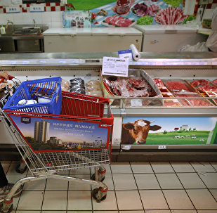 A woman pushes her shopping cart past a display of domestically produced Chinese beef at a supermarket in Beijing