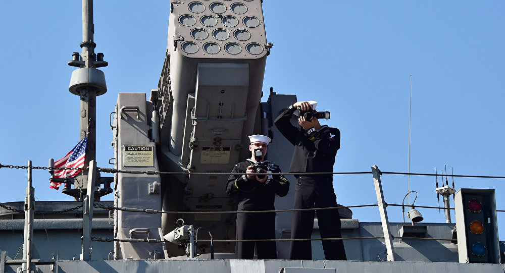 U.S. crew members, standing in front of the RIM-116 launcher, take pictures on the top of the deck of the USS Fort Worth