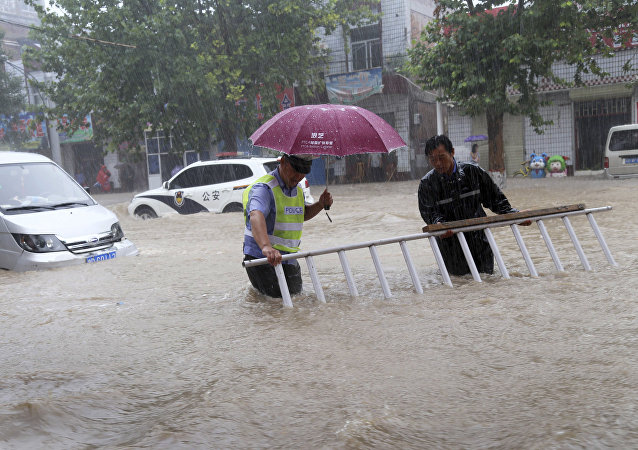 A man helps a traffic policeman move away a barrier on a flooded road in Wanrong County, north China's Shanxi Province
