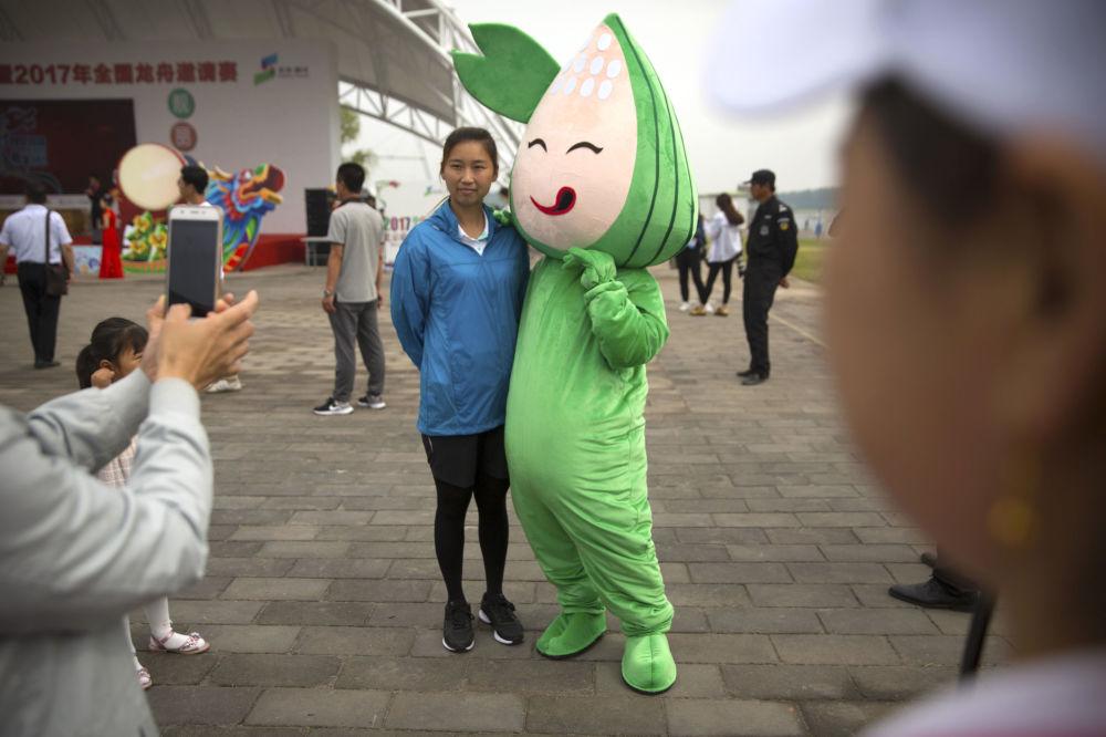 北京龙舟赛期间,一个女孩与粽子吉祥物合影。