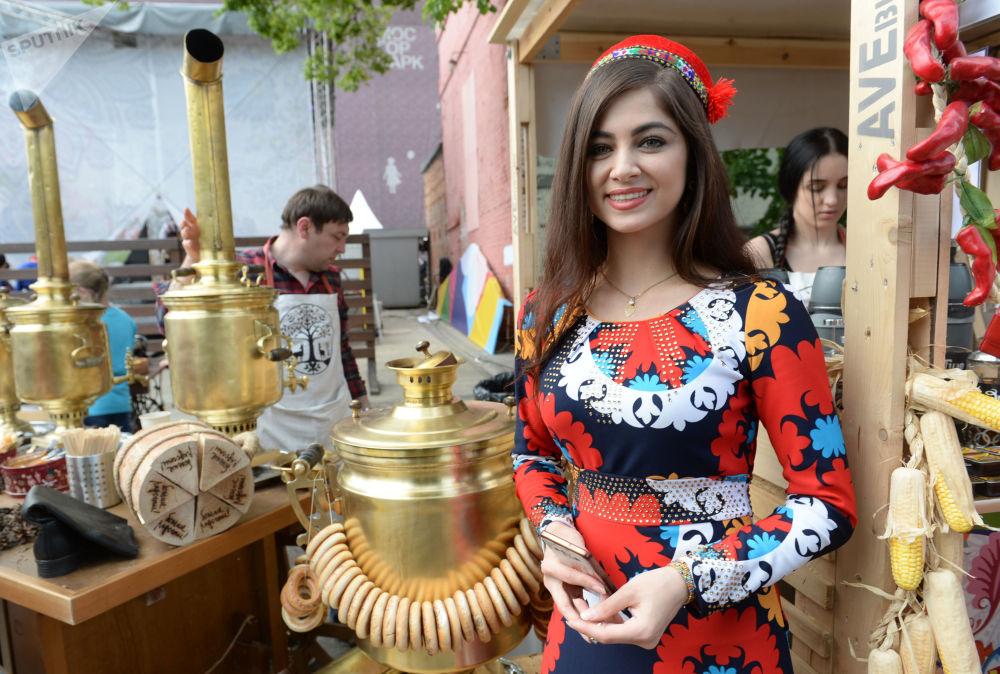 """身穿民族服装的女孩在艾尔米塔什公园举行的""""茶炊联欢节""""上迎接宾客"""