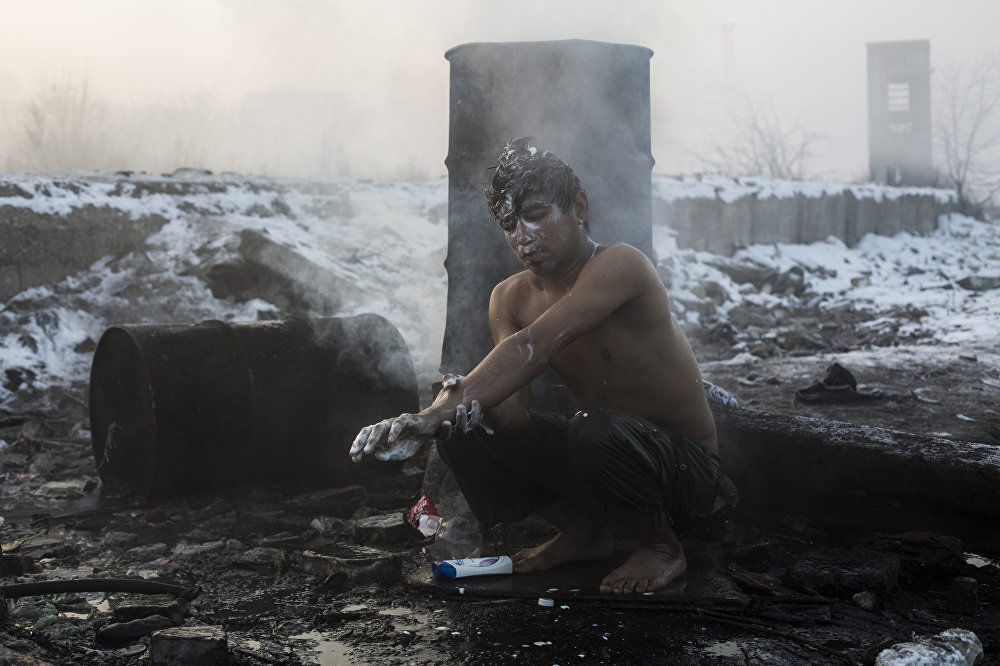 难民在贝尔格莱德的。 亚历山德罗·马丁内斯·韦列斯,西班牙。 图为:一名青年在为住在贝尔格莱德火车站废弃仓库附近的阿富汗和巴基斯坦难民烧水的一个大桶里洗澡。