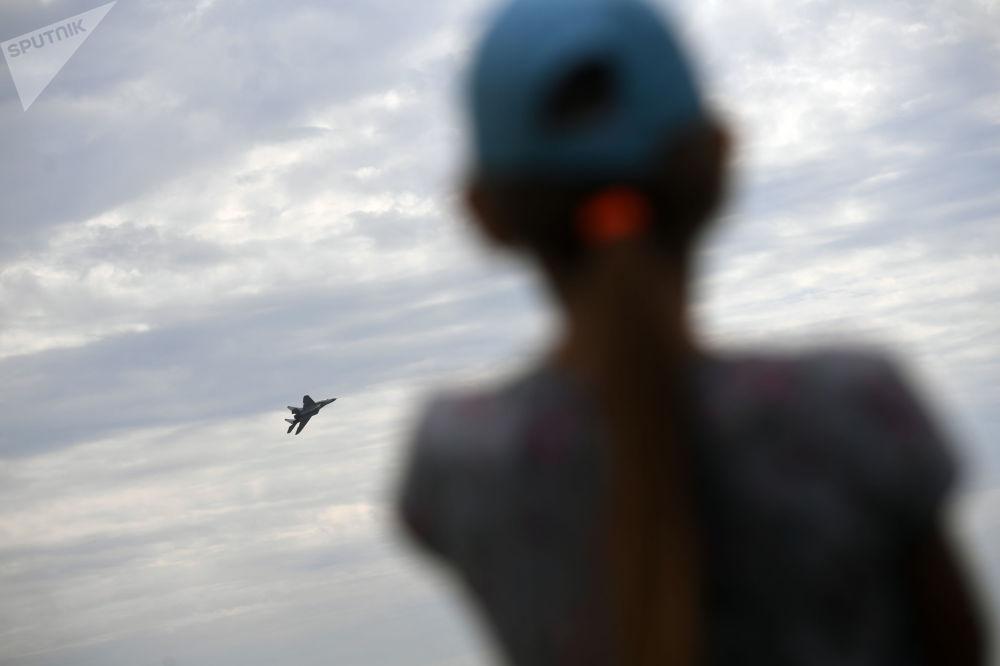 一個女孩正在觀看其中一架參展飛機進行飛行訓練。