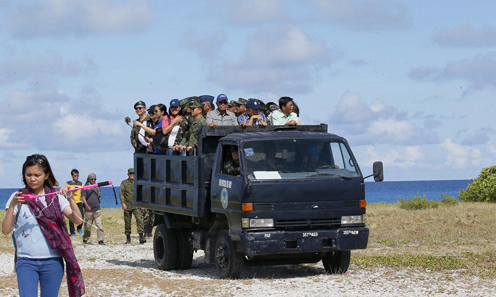 菲律宾国防部长德尔芬·洛伦扎纳(右三)、菲律宾武装部队总参谋长埃德瓦尔多·阿诺(右四)及其他官员登上菲律宾宣称拥有主权的中业岛