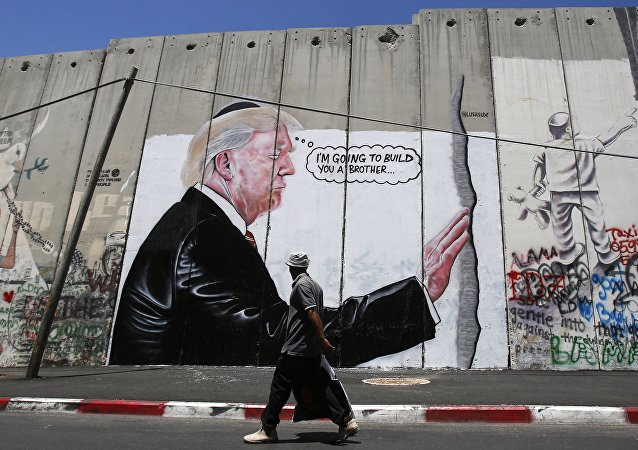 A Palestinian man walks past graffiti depicting US President Donald Trump on the controversial Israeli separation barrier