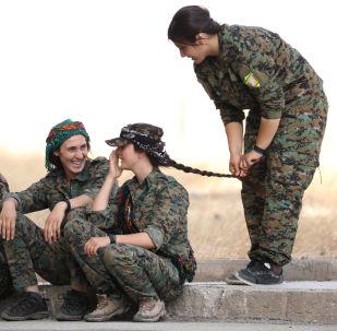 敘利亞民主軍軍人坐在哈薩卡市的路邊。