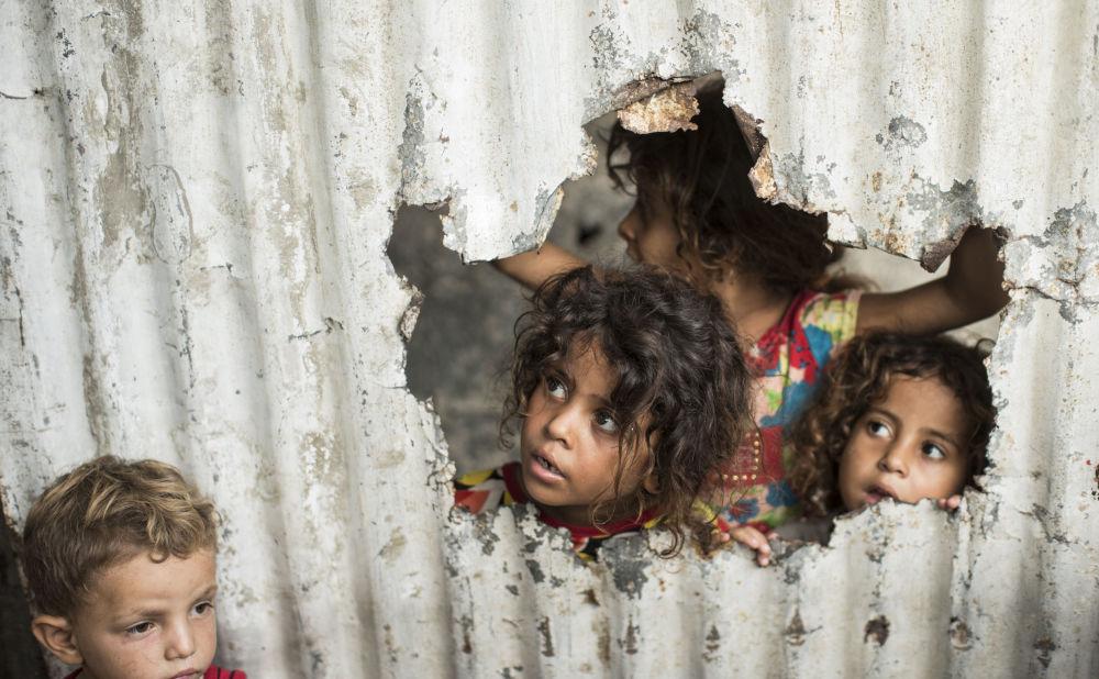加沙一個貧民區,巴勒斯坦兒童通過金屬板柵欄上的口子向外看