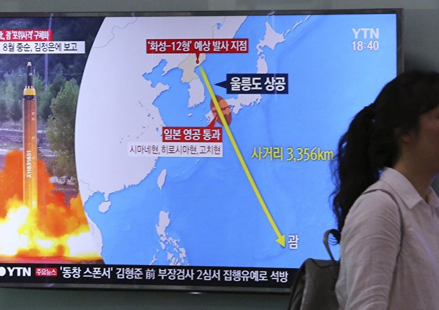 A woman passes by a TV screen showing a local news program reporting on North Korea's threats to strike Guam with missiles