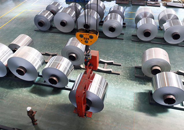 An employee looks at an aluminium foil roll being lifted at a plant in Binzhou, Shandong province, China