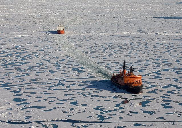 """""""俄罗斯""""号破冰船破开冰层,紧随其后的是载有考察队员和两艘深潜探测器的""""费多罗夫院士""""号科考船。"""