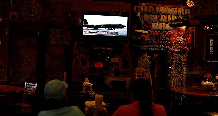 关岛居民在餐馆里收看有关朝鲜半岛危机的新闻