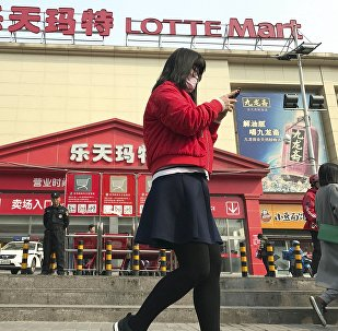 Residents walk past a Lotte Mart in Beijing