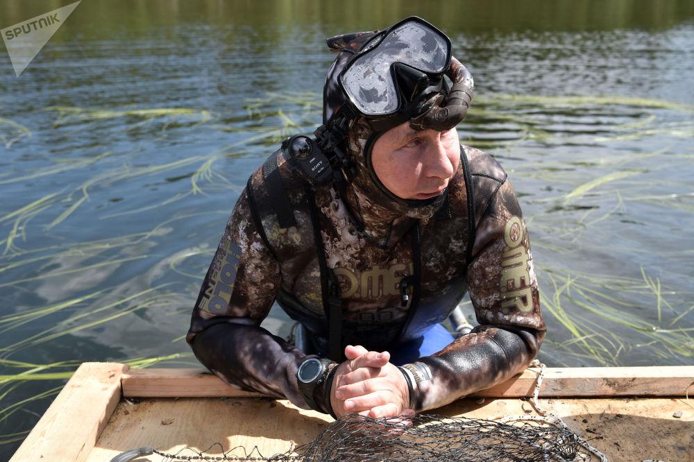 俄罗斯总统普京身穿潜水服在图瓦共和国高山湖泊中潜到水下捕鱼。