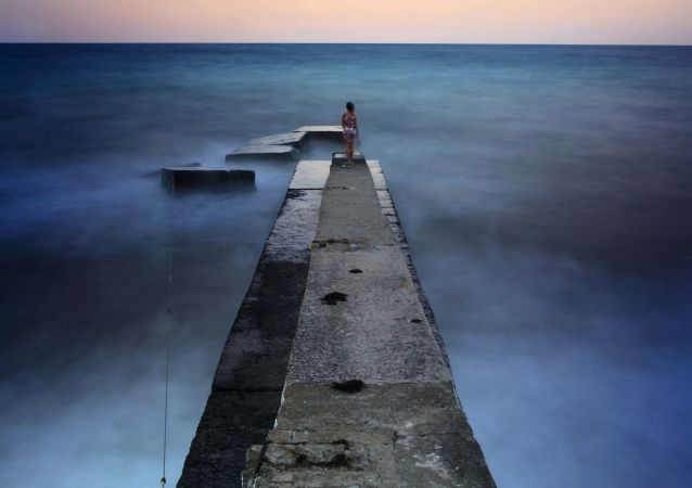 一女孩站在阿卢什塔的防波堤上