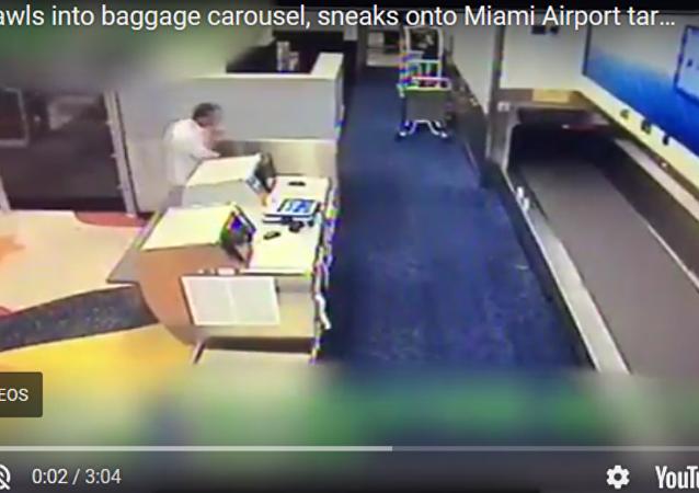 美国迈阿密机场一名乘客通过行李传送带进入机场跑道