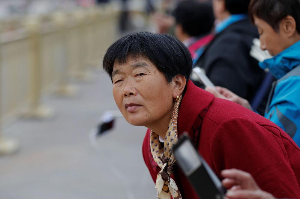 在美國總統唐納德·特朗普的車隊駛過北京天安門廣場時,遊客們企圖看一眼美國總統