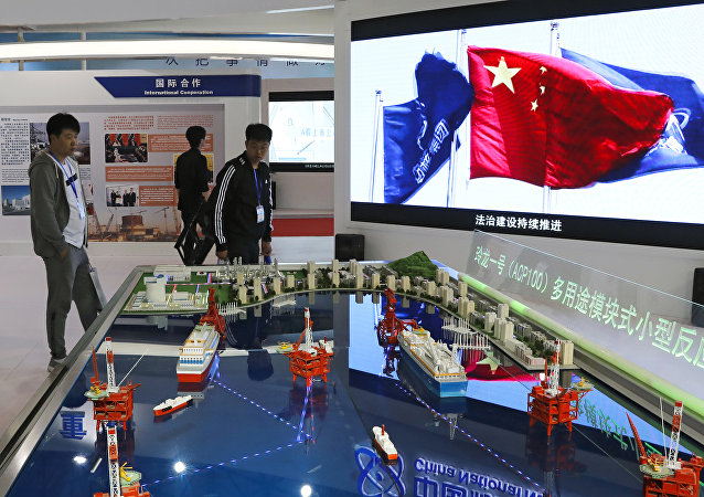 Visitors look at the models of oil tanker shaped floating nuclear reactors and oil rigs showcased at the display booth of China's state-owned China National Nuclear Corporation