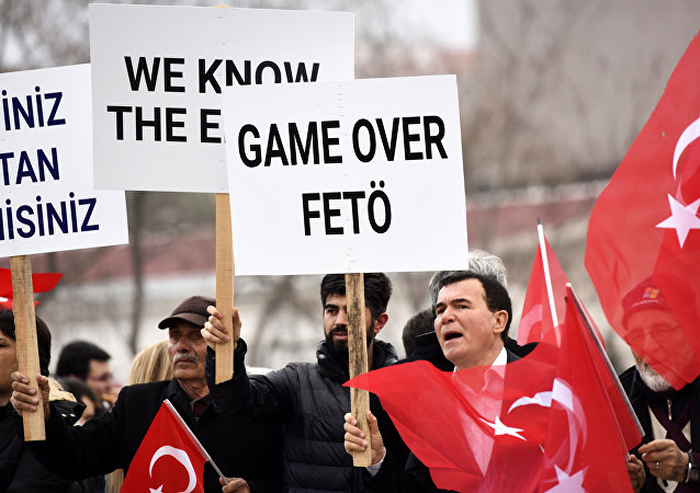 Turkish protestors chant slogans and a man (R) holds a placard reading '''Game over Feto''
