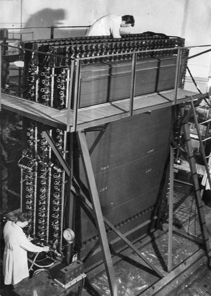 """国家核大学人员调整电离热量计(1964年)。 """"铁""""的重量是40吨,因此量热计的制作和安装,在被固定在圆形实验室天花板下的口号下进行:""""物理学家必须用身体工作!"""""""