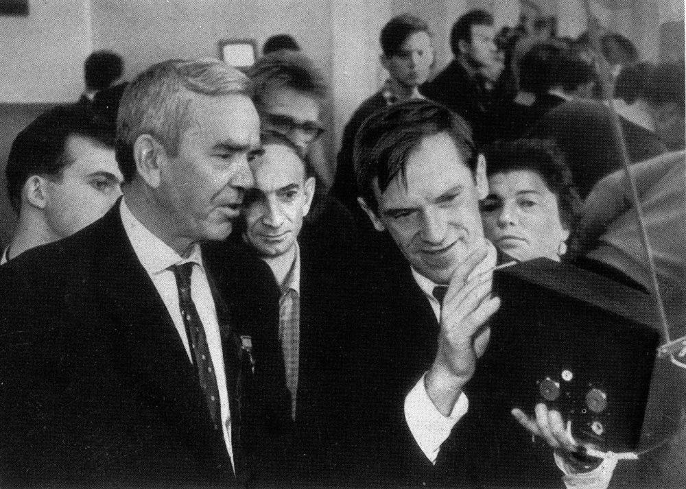 """国家核大学工作人员加布里埃尔·尼古拉耶维奇· 阿列克萨科夫,向苏联极地探险家科伦科尔展示,由他开发的紧凑型晶体管电视""""孔雀石""""(1964年)。 """"孔雀石""""并没有成为工业消费品领域的传奇,而是帮助克服了""""可能—不可能""""的思维定式,这对于国内电子业的发展是有益的。"""