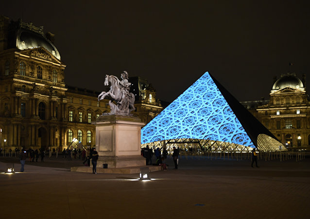 Images are projected onto the Louvre Pyramid in Paris at night