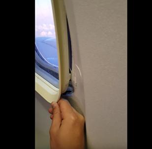 男子坐飞机发现舷窗内侧松动