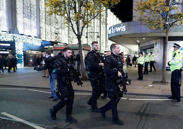 Armed police officers walk along Oxford Street, London