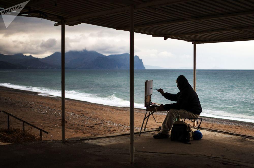 克里米亞塞瓦斯托波爾的一位畫家正在一處沙灘上畫畫