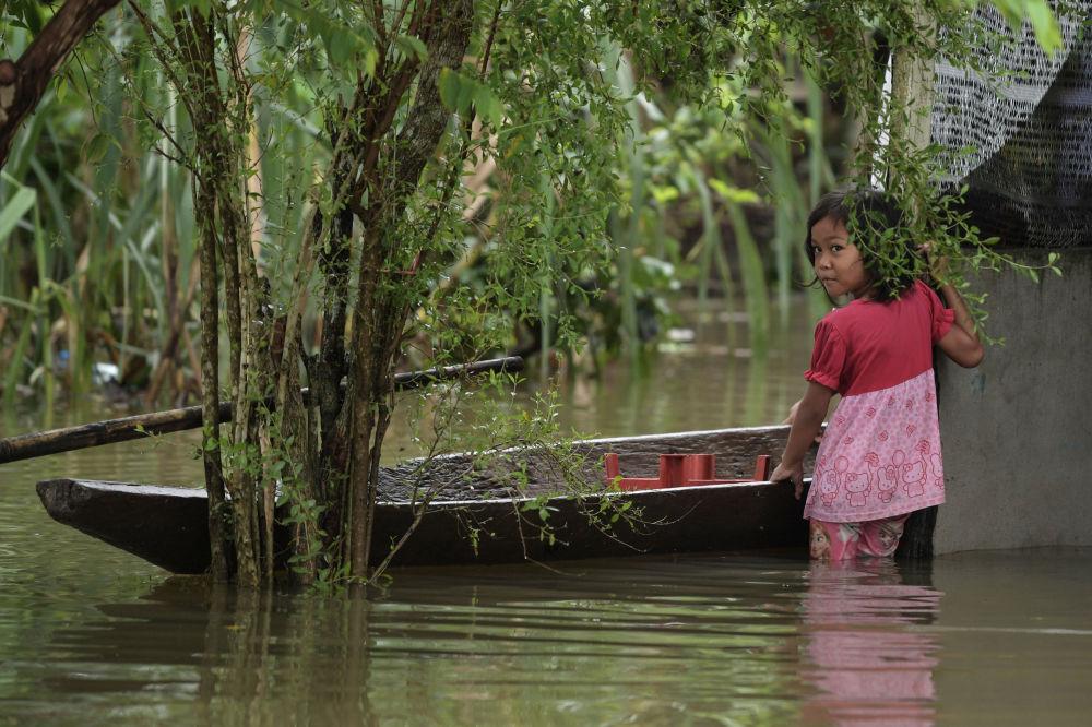 马来西亚遇洪水袭击,图为一名小女孩站在一艘小船旁