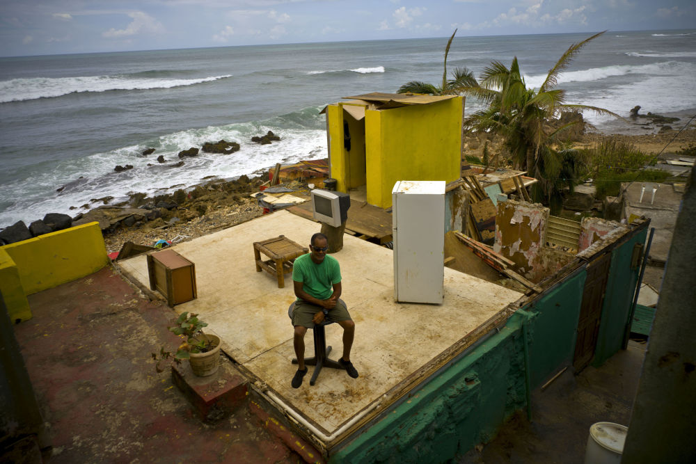 """飓风""""玛丽亚""""肆虐波多黎各,一名男子坐在自家支离破碎的房屋中"""