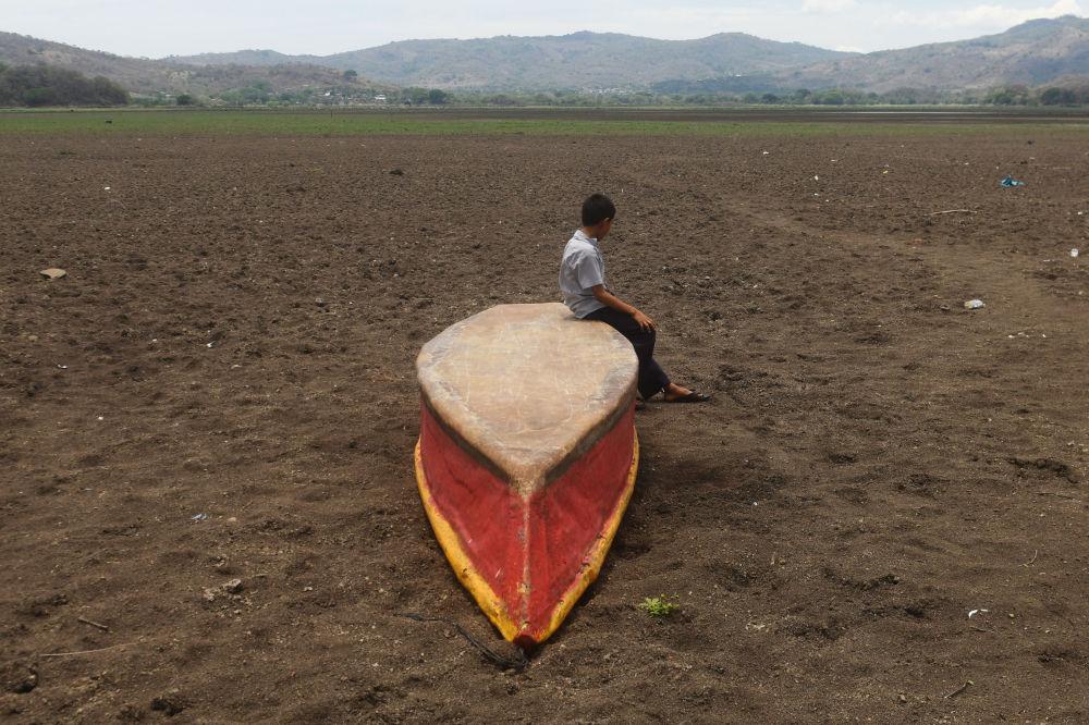 危地马拉阿特斯卡滕帕湖边,一个男孩坐在倒扣的船上凝视着干涸的水域。